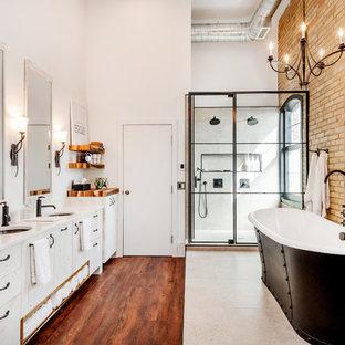 На фото: главная ванная комната в стиле лофт с плоскими фасадами, искусственно-состаренными фасадами, отдельно стоящей ванной, двойным душем, серой плиткой, керамической плиткой, белыми стенами, полом из ламината, врезной раковиной, столешницей из кварцита, коричневым полом, душем с распашными дверями и белой столешницей
