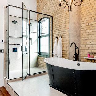 他の地域のインダストリアルスタイルのおしゃれなマスターバスルーム (フラットパネル扉のキャビネット、ヴィンテージ仕上げキャビネット、置き型浴槽、ダブルシャワー、一体型トイレ、グレーのタイル、セラミックタイル、白い壁、ラミネートの床、アンダーカウンター洗面器、珪岩の洗面台、茶色い床、開き戸のシャワー、白い洗面カウンター) の写真