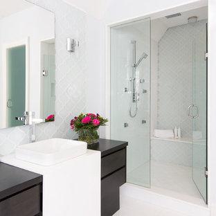 Foto di una stanza da bagno contemporanea con lavabo a bacinella, ante lisce, ante in legno bruno, doccia alcova, piastrelle blu, piastrelle di vetro e pavimento in marmo