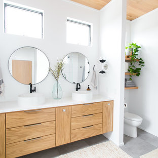 Bathroom - mid-sized contemporary master porcelain floor and gray floor bathroom idea in Cleveland with flat-panel cabinets, light wood cabinets, a two-piece toilet, white walls, a vessel sink, quartz countertops and white countertops