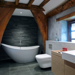 Design ideas for a medium sized country bathroom in Devon with a console sink, a freestanding bath, a built-in shower, a wall mounted toilet, grey tiles, stone tiles, grey walls and porcelain flooring.