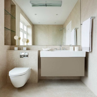 Contemporary shower room in London with flat-panel cabinets, beige cabinets, a wall mounted toilet, beige tiles, beige walls, an integrated sink, beige floors and white worktops.
