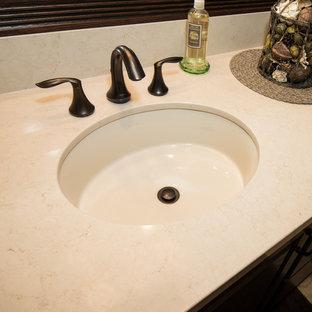 Idee per una stanza da bagno con lavabo sottopiano, ante con bugna sagomata, ante marroni, top in quarzo composito, vasca ad alcova, WC a due pezzi, piastrelle beige, piastrelle in gres porcellanato, pareti beige e pavimento in gres porcellanato