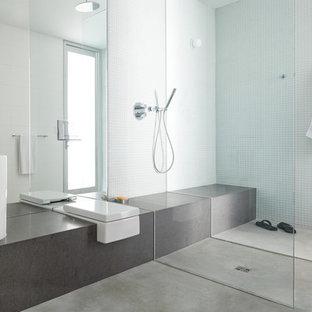 Diseño de cuarto de baño minimalista con lavabo sobreencimera, baldosas y/o azulejos de vidrio, paredes blancas, suelo de cemento y ducha a ras de suelo
