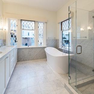 Diseño de cuarto de baño principal, de estilo americano, de tamaño medio, con armarios tipo vitrina, bañera exenta, ducha esquinera, baldosas y/o azulejos grises, baldosas y/o azulejos de mármol, paredes blancas, suelo de mármol y encimera de mármol