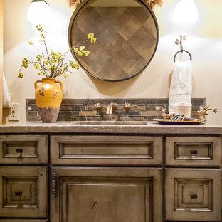 Esempio di una stanza da bagno padronale rustica di medie dimensioni con lavabo integrato, ante con bugna sagomata, ante con finitura invecchiata, top in cemento, WC monopezzo, piastrelle grigie, piastrelle in gres porcellanato, pareti gialle e pavimento con piastrelle in ceramica