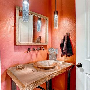 Foto de cuarto de baño con ducha, rústico, pequeño, con lavabo sobreencimera, armarios abiertos, puertas de armario de madera oscura, encimera de madera, parades naranjas y suelo de madera en tonos medios