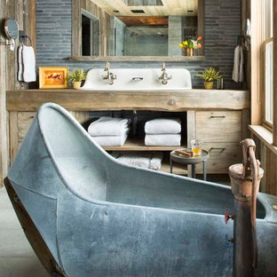 Inspiration for a rustic gray tile freestanding bathtub remodel in Denver with flat-panel cabinets, light wood cabinets, wood countertops and brown countertops