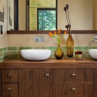 Modelo de cuarto de baño rústico, de tamaño medio, con lavabo sobreencimera, puertas de armario de madera oscura, encimera de madera, baldosas y/o azulejos verdes, baldosas y/o azulejos de cerámica, paredes beige y suelo de baldosas de cerámica