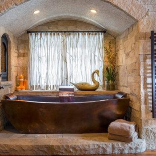 Immagine di una stanza da bagno padronale rustica con piastrelle in pietra e vasca freestanding