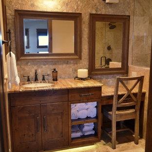 デンバーの中サイズのラスティックスタイルのおしゃれなバスルーム (浴槽なし) (アンダーカウンター洗面器、シェーカースタイル扉のキャビネット、濃色木目調キャビネット、アルコーブ型シャワー、ベージュのタイル、石タイル、ベージュの壁、トラバーチンの床、珪岩の洗面台、ベージュの床、開き戸のシャワー) の写真