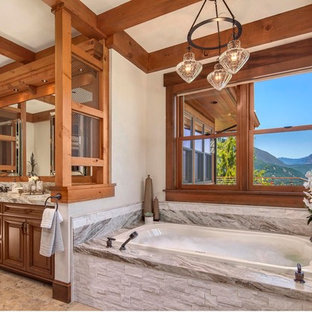 Drop-in bathtub - rustic drop-in bathtub idea in Other with an undermount sink, raised-panel cabinets, medium tone wood cabinets and white walls