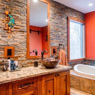 Foto de cuarto de baño principal, rural, con armarios con paneles con relieve, puertas de armario de madera oscura, bañera encastrada, baldosas y/o azulejos de piedra, parades naranjas, lavabo sobreencimera, suelo beige y encimeras multicolor