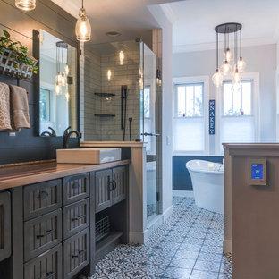 Modelo de cuarto de baño principal, rural, de tamaño medio, con armarios con paneles empotrados, puertas de armario marrones, bañera exenta, ducha esquinera, paredes azules, suelo con mosaicos de baldosas, lavabo sobreencimera, encimera de madera, suelo azul, ducha con puerta con bisagras, encimeras marrones y baldosas y/o azulejos blancos