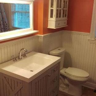 ニューヨークのラスティックスタイルのおしゃれな浴室 (フラットパネル扉のキャビネット、茶色いキャビネット、分離型トイレ、オレンジの壁、一体型シンク、珪岩の洗面台) の写真