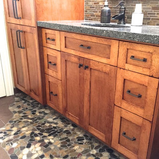 Example of a small mountain style 3/4 multicolored tile and mosaic tile pebble tile floor bathroom design in New York with shaker cabinets, medium tone wood cabinets, a two-piece toilet, beige walls, an undermount sink and granite countertops
