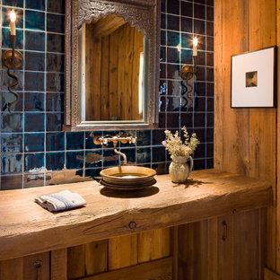 Foto di una stanza da bagno rustica con lavabo a bacinella, ante lisce, ante in legno scuro, piastrelle blu, piastrelle in ceramica e pavimento in legno massello medio
