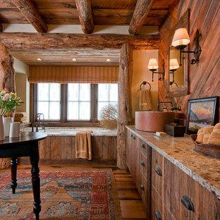 Ejemplo de cuarto de baño rústico con armarios con paneles lisos, puertas de armario de madera en tonos medios, bañera encastrada sin remate, paredes beige y suelo de madera oscura