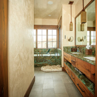 Esempio di una stanza da bagno rustica con ante lisce, ante in legno scuro, vasca sottopiano, pareti beige, lavabo sottopiano, pavimento grigio e top verde