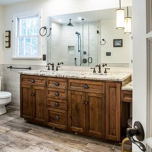 Imagen de cuarto de baño principal, rural, grande, con puertas de armario de madera en tonos medios, ducha esquinera, sanitario de dos piezas, baldosas y/o azulejos beige, baldosas y/o azulejos de porcelana, paredes grises, suelo de baldosas de porcelana, lavabo bajoencimera, encimera de granito, suelo gris, ducha con puerta con bisagras y armarios estilo shaker