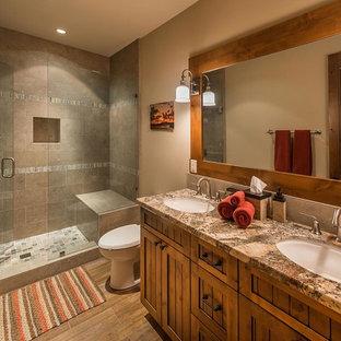 Modelo de cuarto de baño rural con lavabo bajoencimera, armarios estilo shaker, puertas de armario de madera oscura, ducha empotrada, baldosas y/o azulejos grises y paredes marrones