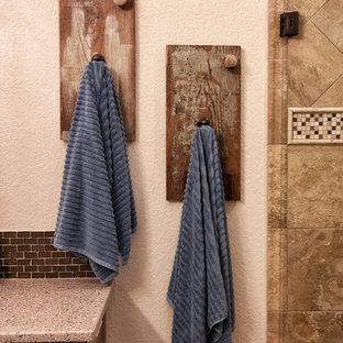 Diseño de cuarto de baño principal, rústico, de tamaño medio, con armarios con paneles empotrados, puertas de armario beige, paredes beige, suelo de corcho, bañera empotrada, ducha empotrada, baldosas y/o azulejos marrones, azulejos en listel, lavabo bajoencimera y encimera de cuarzo compacto
