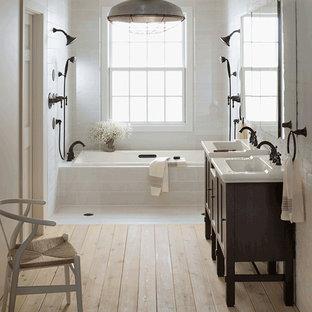 Rustik inredning av ett mellanstort en-suite badrum, med luckor med infälld panel, skåp i mörkt trä, ett platsbyggt badkar, en kantlös dusch, en toalettstol med hel cisternkåpa, beige kakel, porslinskakel, beige väggar, ljust trägolv, ett konsol handfat, granitbänkskiva och beiget golv