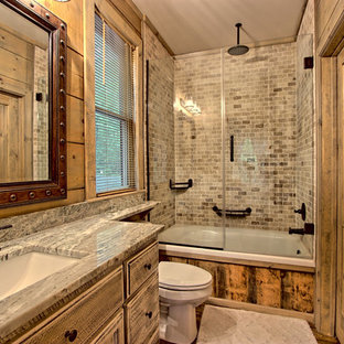 Small mountain style master multicolored tile and stone tile painted wood floor and brown floor bathroom photo in Other with recessed-panel cabinets, distressed cabinets, a two-piece toilet, gray walls, a drop-in sink, granite countertops and a hinged shower door