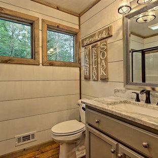 Imagen de cuarto de baño rural, pequeño, con armarios con paneles empotrados, puertas de armario grises, sanitario de dos piezas, paredes blancas, suelo de madera pintada, lavabo encastrado, encimera de granito, suelo marrón y ducha con puerta con bisagras