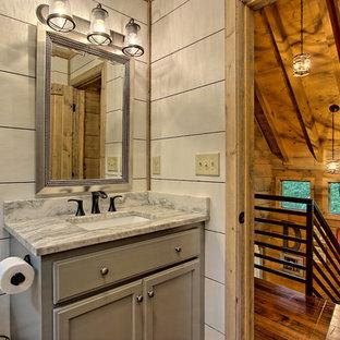 Foto de cuarto de baño rústico, pequeño, con armarios con paneles empotrados, puertas de armario grises, sanitario de dos piezas, paredes blancas, suelo de madera pintada, lavabo encastrado, encimera de granito, suelo marrón y ducha con puerta con bisagras