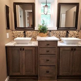 Salle de bain avec une plaque de galets et un sol en bois brun ...