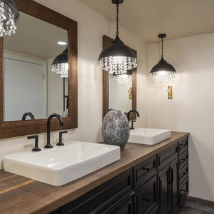Modelo de cuarto de baño principal, rural, grande, con armarios con paneles empotrados, puertas de armario negras, paredes blancas, suelo de madera pintada, lavabo sobreencimera, encimera de madera, suelo marrón y encimeras marrones