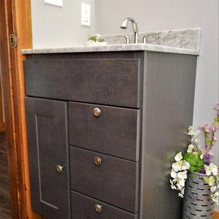 Ejemplo de cuarto de baño con ducha, único y de pie, rural, pequeño, con armarios estilo shaker, puertas de armario grises, paredes azules, suelo laminado, lavabo integrado, encimera de granito, suelo marrón y encimeras grises