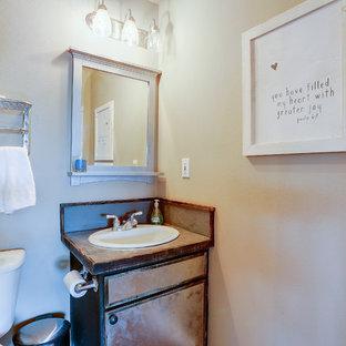 Foto de cuarto de baño rústico, pequeño, con puertas de armario con efecto envejecido, armarios con paneles lisos, sanitario de una pieza, lavabo encastrado, encimera de acero inoxidable, encimeras grises y paredes beige