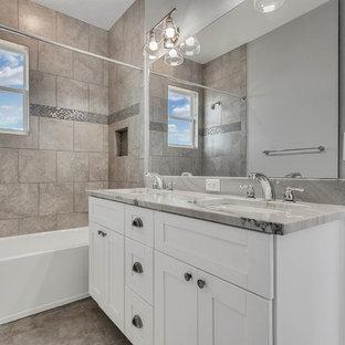 Foto de cuarto de baño principal, campestre, grande, con armarios estilo shaker, puertas de armario blancas, bañera encastrada, combinación de ducha y bañera, sanitario de una pieza, baldosas y/o azulejos grises, baldosas y/o azulejos con efecto espejo, paredes grises, suelo de baldosas de porcelana, lavabo bajoencimera, encimera de cuarzo compacto, suelo gris, ducha abierta y encimeras grises