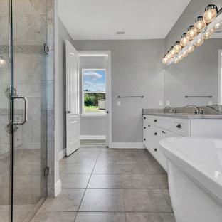 Foto de cuarto de baño principal, de estilo de casa de campo, grande, con armarios estilo shaker, puertas de armario blancas, bañera exenta, ducha abierta, sanitario de una pieza, baldosas y/o azulejos grises, baldosas y/o azulejos con efecto espejo, paredes grises, suelo de baldosas de porcelana, lavabo bajoencimera, encimera de cuarzo compacto, suelo gris, ducha abierta y encimeras grises