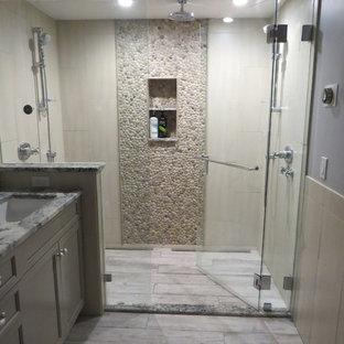 Immagine di una stanza da bagno padronale tradizionale di medie dimensioni con lavabo sottopiano, ante con riquadro incassato, ante grigie, top in granito, doccia alcova, WC sospeso, piastrelle multicolore, piastrelle di ciottoli, pareti blu e pavimento in gres porcellanato
