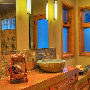 シアトルの中サイズのラスティックスタイルのおしゃれなマスターバスルーム (ベッセル式洗面器、フラットパネル扉のキャビネット、中間色木目調キャビネット、コンクリートの洗面台、オープン型シャワー、分離型トイレ、マルチカラーのタイル、石タイル、緑の壁、スレートの床) の写真