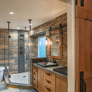 オマハのラスティックスタイルのおしゃれなマスターバスルーム (シェーカースタイル扉のキャビネット、中間色木目調キャビネット、置き型浴槽、オープン型シャワー、茶色いタイル、石タイル、ソープストーンの洗面台) の写真