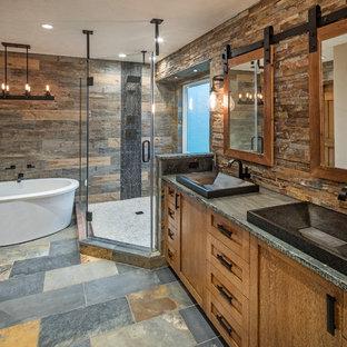 Diseño de cuarto de baño principal, rural, con armarios estilo shaker, puertas de armario de madera oscura, bañera exenta, ducha abierta, baldosas y/o azulejos marrones, baldosas y/o azulejos de piedra y encimera de esteatita