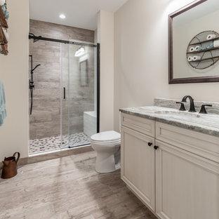 Idee per una stanza da bagno con doccia chic di medie dimensioni con ante con riquadro incassato, ante beige, WC a due pezzi, piastrelle in gres porcellanato, pareti beige, pavimento in gres porcellanato, lavabo sottopiano, top in quarzo composito, doccia alcova, piastrelle beige, pavimento beige, porta doccia scorrevole e top grigio