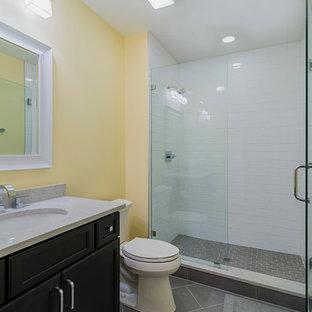 Ejemplo de cuarto de baño con ducha, clásico renovado, de tamaño medio, con puertas de armario de madera en tonos medios, ducha empotrada, sanitario de dos piezas, baldosas y/o azulejos grises, baldosas y/o azulejos de porcelana, paredes amarillas, suelo de baldosas de porcelana, lavabo bajoencimera, armarios con paneles empotrados y encimera de mármol