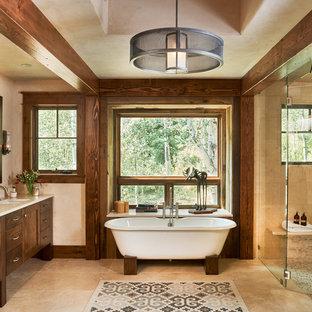 Rustikales Badezimmer En Suite mit Schrankfronten im Shaker-Stil, dunklen Holzschränken, freistehender Badewanne, bodengleicher Dusche, beigefarbenen Fliesen, Unterbauwaschbecken, Granit-Waschbecken/Waschtisch und Travertinfliesen in Denver