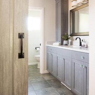 Inspiration pour une grande salle de bain principale traditionnelle avec un placard à porte shaker, des portes de placard bleues, une baignoire encastrée, un espace douche bain, un WC séparé, un carrelage vert, du carrelage en ardoise, un mur blanc, un sol en carrelage de porcelaine, un lavabo encastré, un plan de toilette en quartz modifié, un sol vert et une cabine de douche à porte battante.