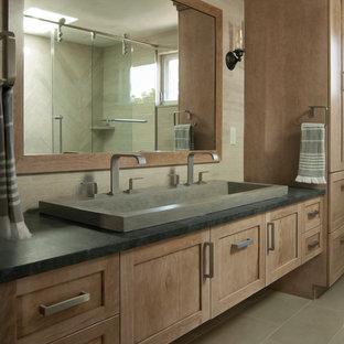 Ejemplo de cuarto de baño principal, minimalista, de tamaño medio, con armarios estilo shaker, puertas de armario de madera clara, ducha empotrada, sanitario de una pieza, baldosas y/o azulejos beige, baldosas y/o azulejos de cerámica, paredes beige, suelo de baldosas de porcelana, lavabo de seno grande, encimera de cemento, suelo marrón, ducha con puerta corredera y encimeras grises