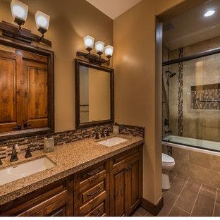 Foto de cuarto de baño rural, de tamaño medio, con armarios con paneles con relieve, puertas de armario de madera oscura, bañera empotrada, sanitario de dos piezas, baldosas y/o azulejos marrones, baldosas y/o azulejos de porcelana, paredes marrones, suelo de baldosas de porcelana, lavabo bajoencimera y encimera de cuarzo compacto