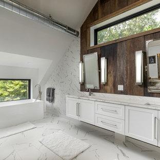 Imagen de cuarto de baño principal, rústico, grande, con puertas de armario blancas, bañera exenta, baldosas y/o azulejos blancos, paredes blancas, lavabo bajoencimera, suelo blanco, encimeras blancas y armarios estilo shaker