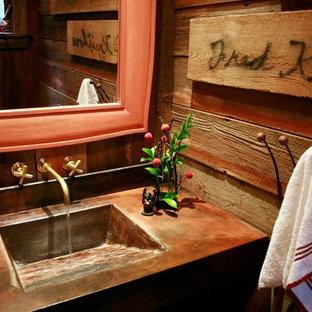 На фото: ванная комната среднего размера в стиле рустика с монолитной раковиной, фасадами с утопленной филенкой, темными деревянными фасадами, столешницей из меди, раздельным унитазом, коричневыми стенами и душевой кабиной с