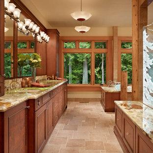 シアトルの巨大なラスティックスタイルのおしゃれなマスターバスルーム (レイズドパネル扉のキャビネット、濃色木目調キャビネット、ドロップイン型浴槽、コーナー設置型シャワー、ベージュのタイル、セラミックタイル、ベージュの壁、セラミックタイルの床、オーバーカウンターシンク、珪岩の洗面台) の写真