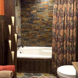 他の地域の中くらいのラスティックスタイルのおしゃれな浴室 (ベッセル式洗面器、珪岩の洗面台、ドロップイン型浴槽、シャワー付き浴槽、分離型トイレ、オレンジの壁、家具調キャビネット) の写真